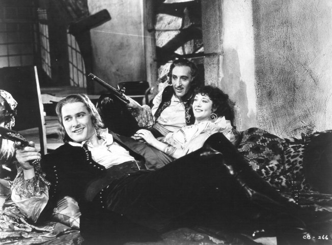 Captain Blood (Errol Flynn) lounging with a couple of friends.